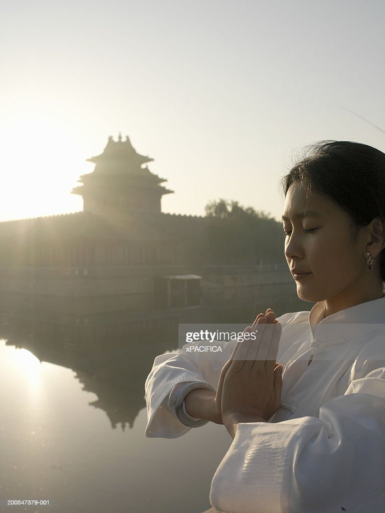 Chinese woman performing tai chi exercises by lake at Forbidden City : Stock Photo