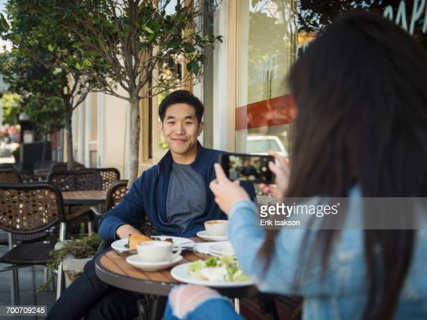 Chinese woman photographing man at outdoor cafe with cell phone