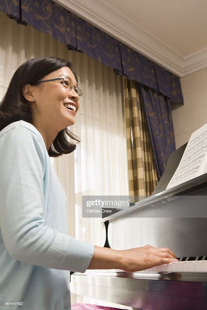 Chinese woman playing piano : Stock Photo