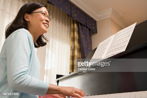 Chinese woman playing piano : Stock Photo