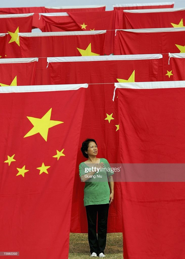 A Chinese woman poses for a photo as she visits a national flag show decorated for the upcoming National Day celebrations at Chaoyang park on September 30, 2006 in Beijing, China. Chinese people are preparing for the 57th anniversary of the founding of People's Republic of China which falls on October 1.
