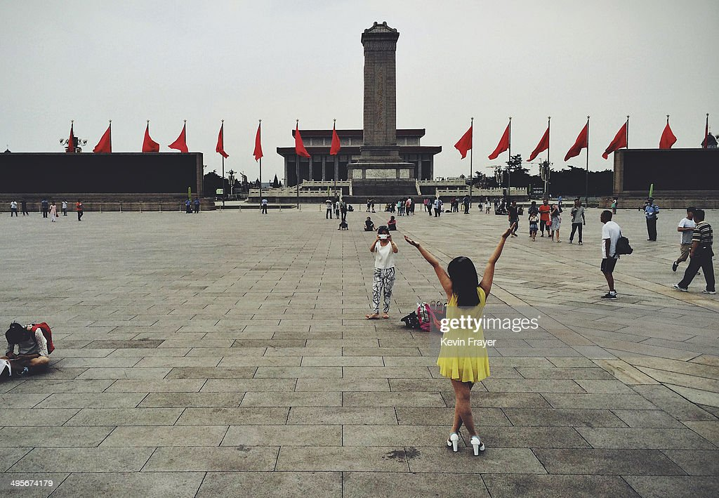 A Chinese woman poses for a picture in Tiananmen Square on June 4, 2014 in Beijing, China. Twenty-five years ago on June 4, 1989 Chinese troops cracked down on pro-democracy protesters, and in the clashes that followed, scores were killed and injured.