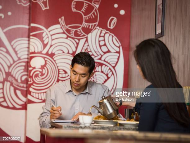 Chinese woman pouring tea in restaurant