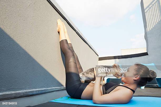 Chinese woman practicing yoga with dog on deck