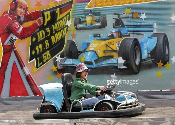 A chinese woman races at a gokart track beneath the car of 2005 F1 world champion Fernando Alsonso in Shanghai 10 October 2005 The city is gearing up...