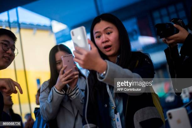 A Chinese woman reacts while setting up the facial recognition feature on her iPhone X inside an Apple showroom in Beijing on November 3 2017 / AFP...