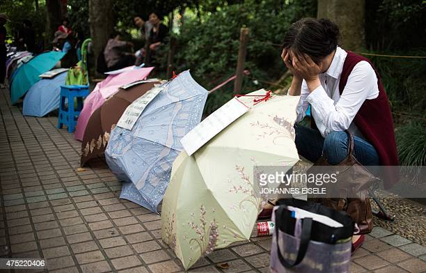 A Chinese woman rests behind her advertising notice set up on an umbrella to attract other parents while looking for a partner for her child at a...