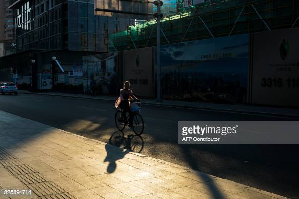 A Chinese woman rides a bicycle along a road in Shanghai on August 3 2017 / AFP PHOTO / CHANDAN KHANNA