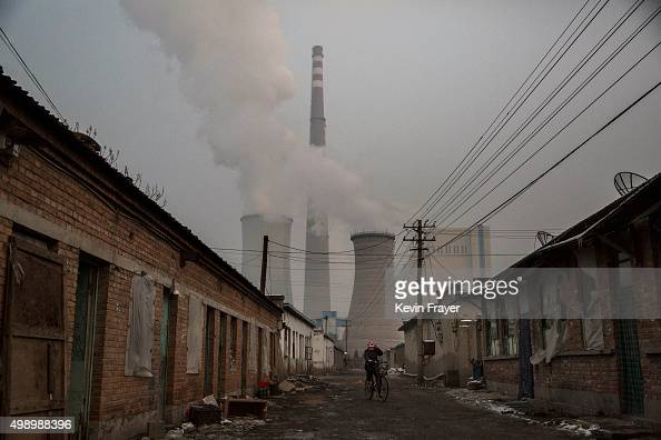 Chinese woman rides her bike near a coal fired power plant on November 27 2015 on the outskirts of Beijing China China's government has set 2030 as a...