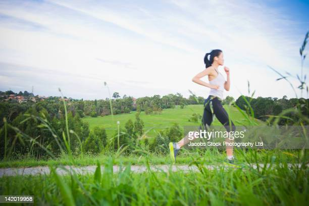 Chinese woman running along path