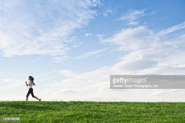 Chinese woman running on hill