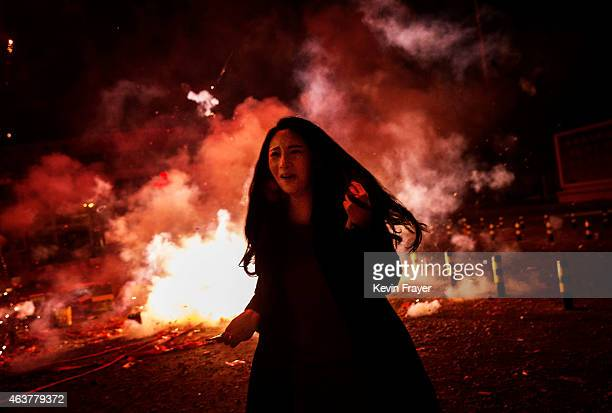 A Chinese woman runs away as she reacts as firecrackers she lit explode during celebrations of the Lunar New early on February 19 2015 in Beijing...