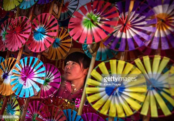 Chinese woman sells traditional handheld windmills at a local temple fair on the fifth day of the Chinese Lunar New Year on February 1 2017 in...