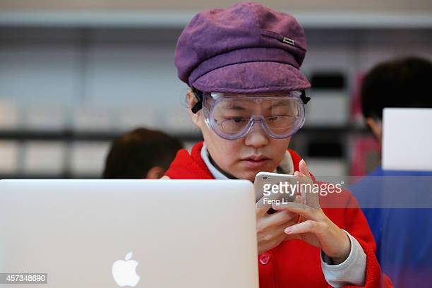 Chinese woman sets up her new iPhone 6 inside an Apple store on October 17 2014 in Beijing China Apple Inc began delivering its popular smartphone...