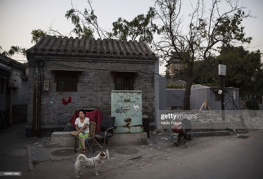 Chinese woman sits with her dog outside her Hutong or traditional home on September 18 2014 in central Beijing China Many of the traditonal homes in...