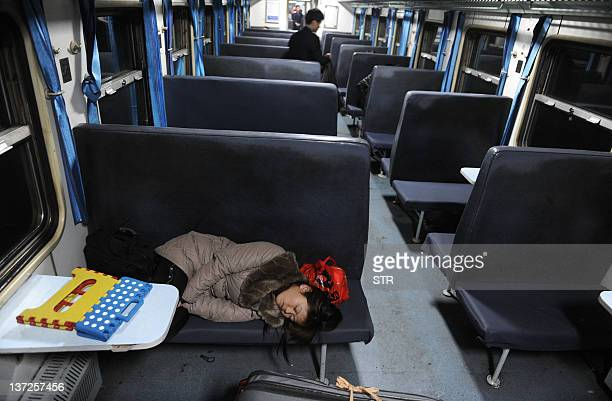 A Chinese woman sleeps on a seat in a train at a railway station in Hefei east China's Anhui province on January 17 as they return home for the lunar...
