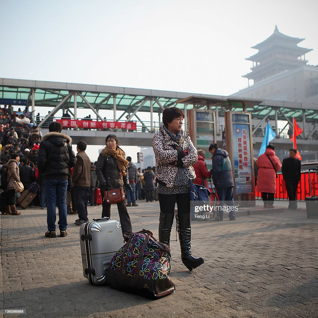 A Chinese woman stands near her luggage outside Beijing West Railway Station on January 8, 2012 in Beijing, China. China's annual Spring Festival travel rush begins on Sunday, and authorities estimate 3.158 billion passenger journeys will be made for the Chinese lunar new year during the 40-day travel period.