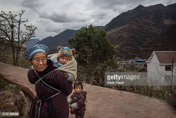 Chinese woman stands with her grandchildren in a village on March 26 2016 in Hanyuan County Sichuan province China Heavy pesticide use on fruit trees...
