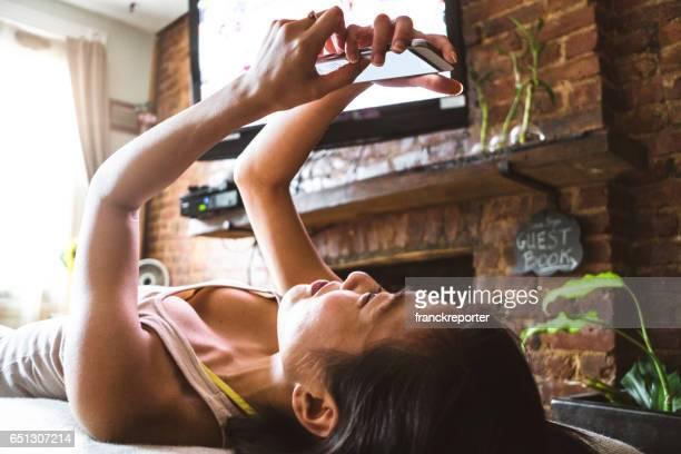 中国の女性がソファーでスマート フォンでのネット サーフィン