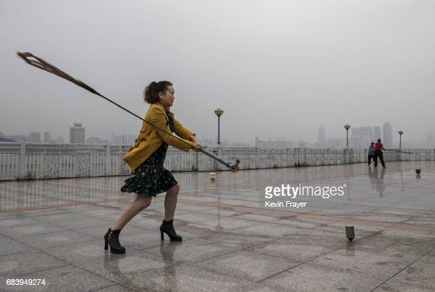 Chinese woman swings as she exercises playing the traditional game of 'whipping top' on a boardwalk near the Great Bridge on the Yangtze River or...