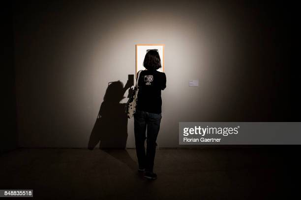 A chinese woman takes a photo with her smartphone of a print at the exhibition 'Deutschland 8' on September 17 2017 in Beijing China 'Deutschland 8'...