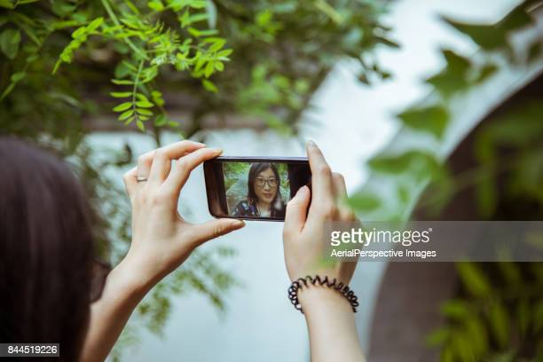 Chinese Woman taking selfie in the park