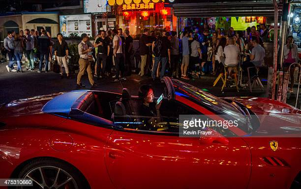 Chinese woman talks on her mobile phone as she drives a luxury car throught a bar district on May 30 2015 in Beijing China China is expected to...