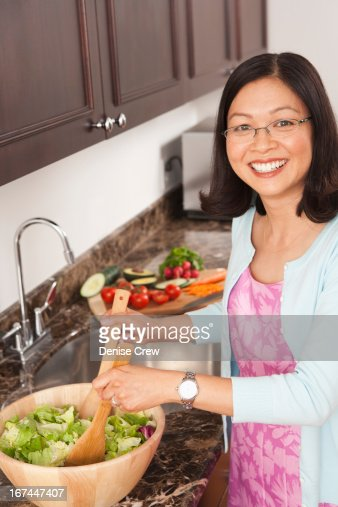 Chinese woman tossing salad in kitchen : Stock Photo