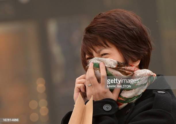 A Chinese woman tries to protect herself as Beijing is hit by a sandstorm as well as air quality worse than the highest classification of 'hazardous'...
