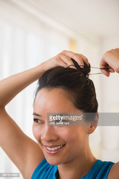 Chinese woman tying her hair in bun