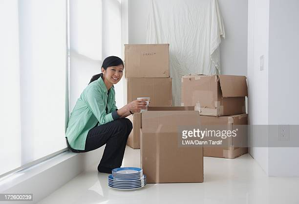 Chinese woman unpacking boxes in new home