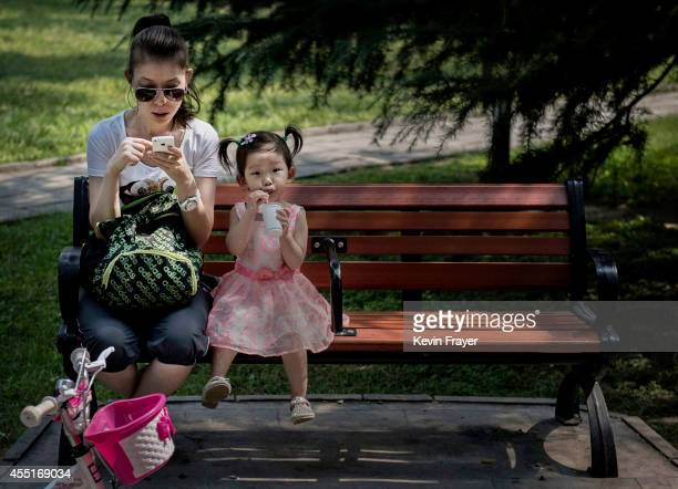 Chinese woman uses her smartphone as her daughter sits beside her on a park bench on September 10 2014 in Beijing China China tightened censorship on...