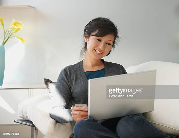 Chinese woman using laptop on sofa