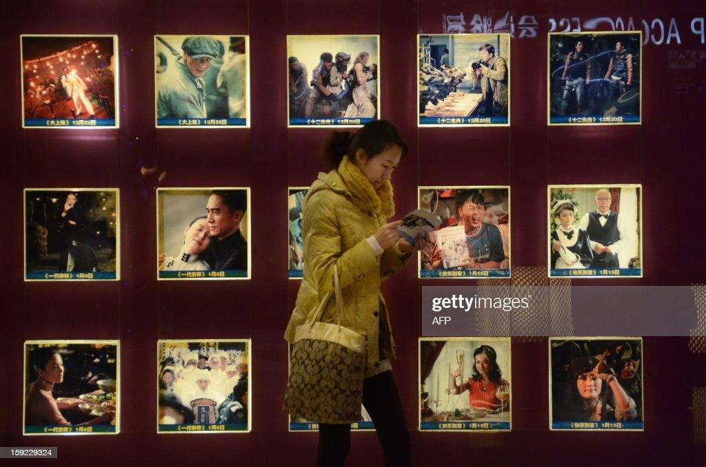 A Chinese woman walks past a set of illuminated movie posters as she reads a pamphlet at a cinema in Beijing on January 10, 2013. Moviegoers in China spent 17 billion yuan (2.7 billion USD) on tickets last year, turning the country into the second-largest film market in the world, the state news agency Xinhua said on January 9.