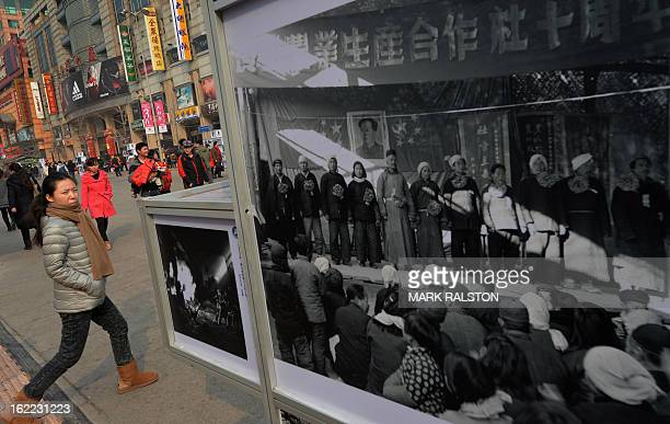 A Chinese woman walks past an exhibition of Cultural Revolution era photos on display at the Wangfujing shopping street in Beijing on February 21...