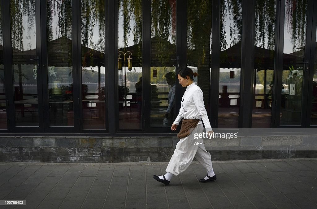 A Chinese woman walks past an outdoor bar in Beijing on November 21, 2012. China's Communist leaders are promising to revolutionise the world's second largest economy and move on from being the world's workshop, but economists say the monumental task faces major hurdles. AFP PHOTO / WANG ZHAO