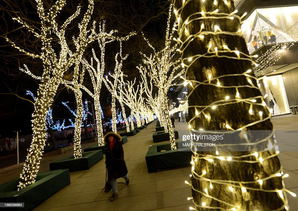 A Chinese woman walks past Christmas decorated trees on display in Beijing on December 10, 2012. Mathematics has provided an answer for those striving for the perfect Christmas tree, Britain's University of Sheffield says after being set the challenge of decorating a tree so that greenery and glitz are in harmonious proportion. Their formula states a 180cm (six-feet) Christmas tree would need 37 baubles, around 919 cms of tinsel (30 feet) and 565 cms (19 feet) of lights, and an 18cm (seven-inch) star or angel to achieve the perfect look. AFP PHOTO/Mark RALSTON
