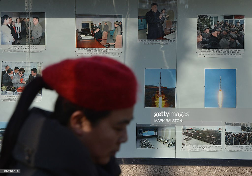 A Chinese woman walks past photos of North Korea's recent rocket launch on display outside the North Korean embassy in Beijing on February 6, 2013. China should exact a 'heavy price' from North Korea if it carries out a planned nuclear test, state-run media said on February 6, in an unusually strongly-worded call for action by Pyongyang's closest ally. AFP PHOTO / Mark RALSTON