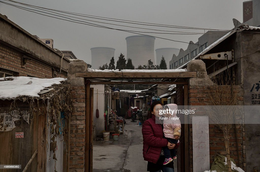 Chinese woman walks with her child from her house next to a coal fired power plant on November 27 2015 on the outskirts of Beijing China China's...