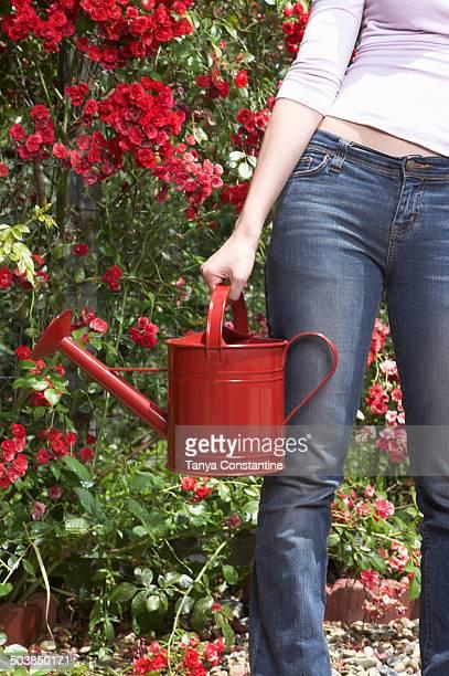 Chinese woman watering plants in backyard