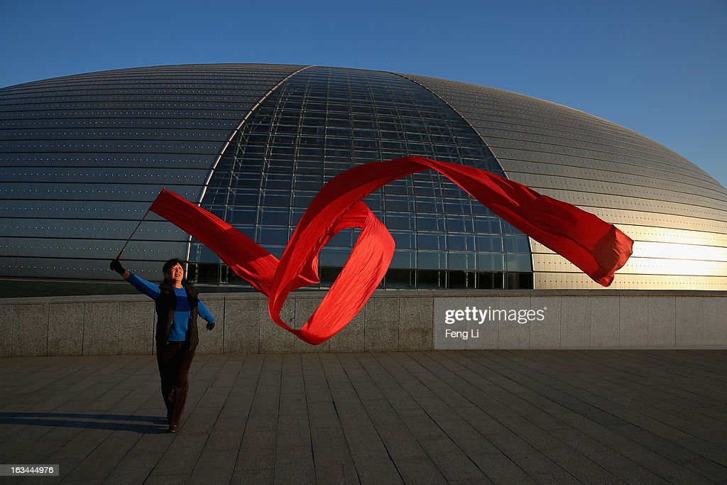 A Chinese woman waves a red ribbon to exercise outside China's National Grand Theater before a plenary session of the National People's Congress on March 10, 2013 in Beijing, China. The State Council, China's cabinet, will begin its seventh restructuring attempt in the past three decades to roll back red tape and reduce administrative intervention. Several departments under the State Council will be reorganized according to a plan on the institutional restructuring and functional transformation of the State Council, which was submitted to the plenary session of the National People's Congress Sunday.
