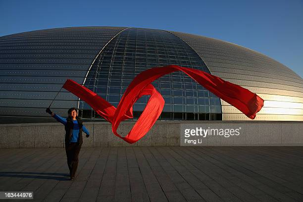 Chinese woman waves a red ribbon to exercise outside China's National Grand Theater before a plenary session of the National People's Congress on...