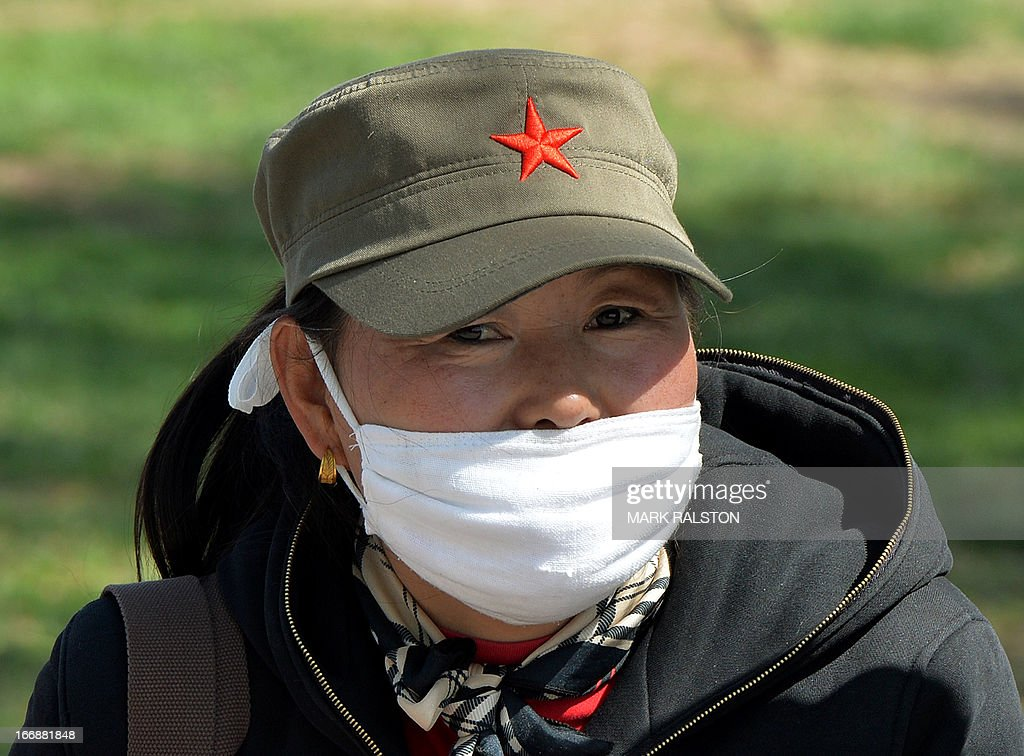 A Chinese woman wears a face mask as the country deals with the H7N9 bird flu virus on April 18, 2013. China has confirmed a total of 82 human cases of H7N9 avian influenza since announcing about two weeks ago that it had found the strain in people for the first time. Health authorities in China say they do not know exactly how the virus is spreading, but it is believed to be crossing to humans from birds, triggering mass poultry culls in several cities. AFP PHOTO/Mark RALSTON