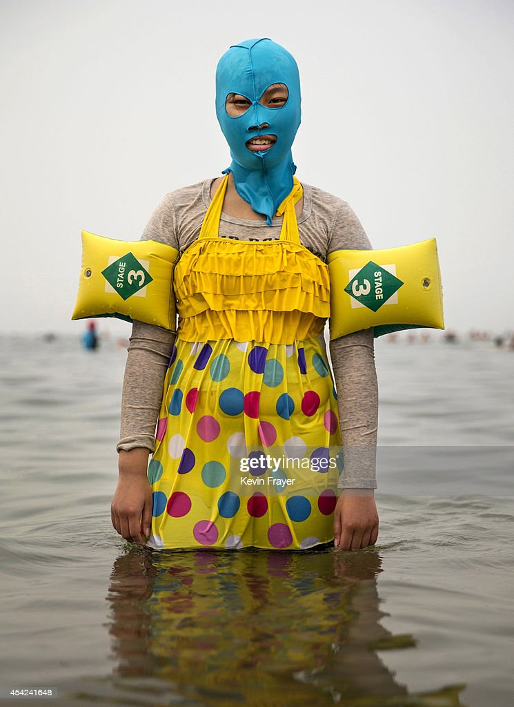 Chinese woman wears a facekini as she poses on August 21 2014 in the Yellow Sea in Qingdao China The locally designed mask is worn by many local...