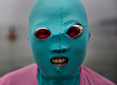 Chinese woman wears a facekini while swimming on August 22 2014 in the Yellow Sea in Qingdao China The locally designed mask is worn by many local...