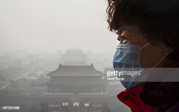 Chinese woman wears a mask as haze from smog caused by air pollution hangs over the Forbidden City on November 15 2015 in Beijing China As a result...