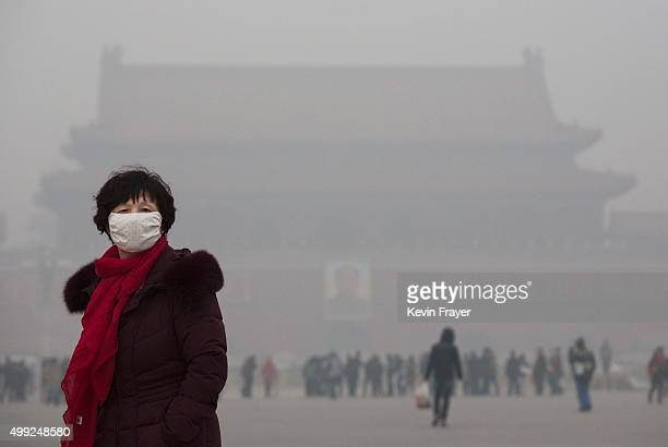 A Chinese woman wears a mask as she walks through a very hazy Tiananmen Square on a day of heavy pollution on November 30 2015 in Beijing China...