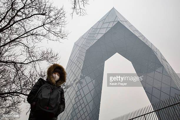 Chinese woman wears a mask to protect against pollution as she passes the CCTV building in heavy smog on December 8 2015 in Beijing China The Beijing...
