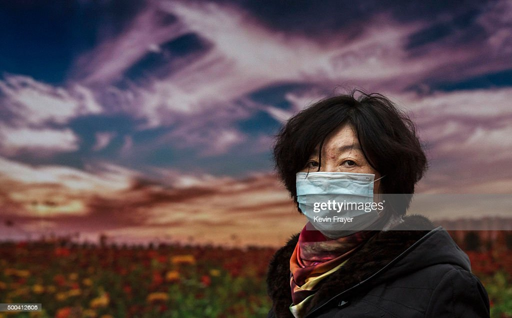 Chinese woman wears a mask to protect against pollution as she passes a picture of a sunset advertising tourism to China's polluted Hebei province at...