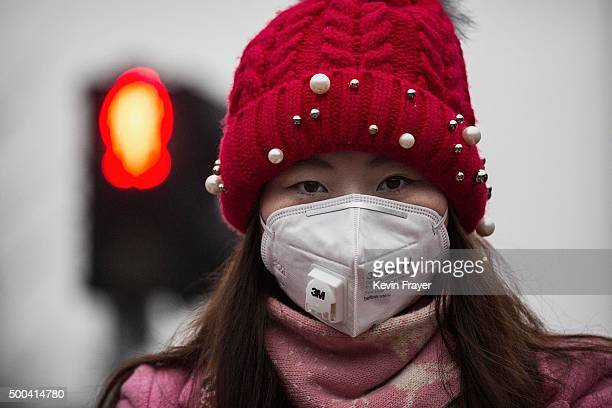 Chinese woman wears a mask to protect against pollution as they wait to cross the street in heavy smog on December 8 2015 in Beijing China The...